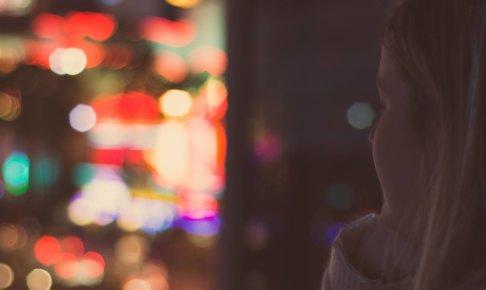 夜景を見つめる居場所を探している女性