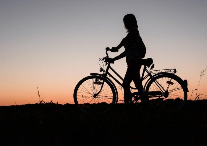 一人夕焼けをバックに自転車を押している女性