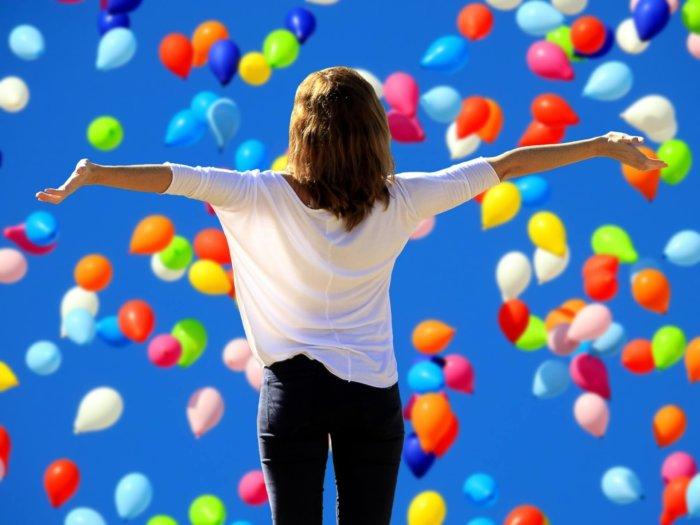 飛んでいる風船。のびのびと両手を広げ開放的な女性