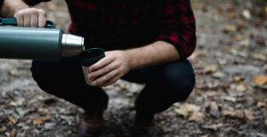 水筒のコップにお茶を注いでいる男性
