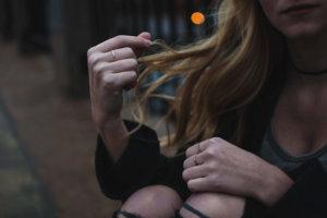 髪をいじって暇をする女性