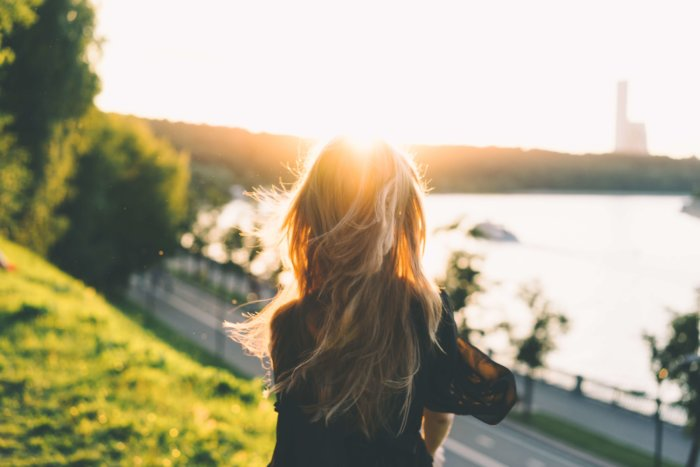 夕日に照らされて背中を向ける女性
