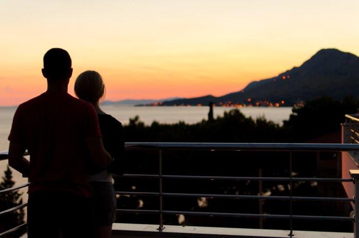 逆光の夕日の中景色を眺めるカップル