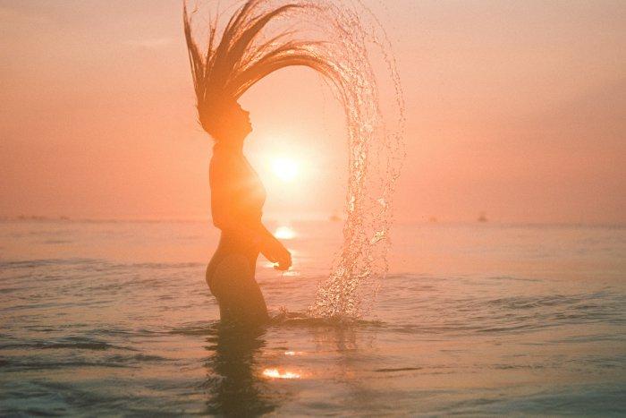 海からあがってしぶきを上げる女性