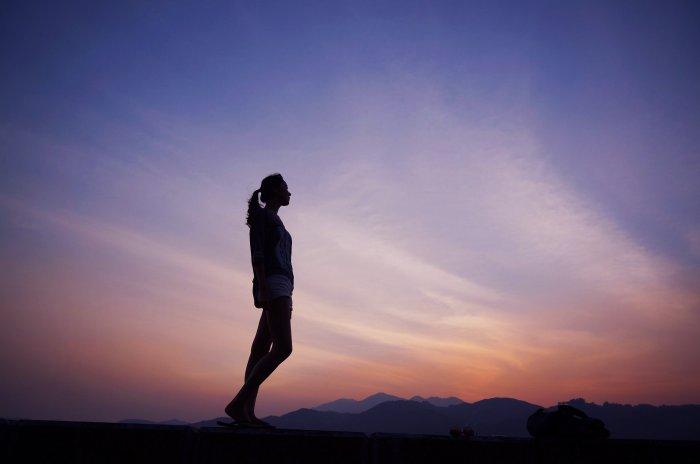 夕暮れ時にたたずみ遠くを見ている女性