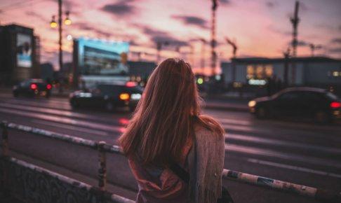 道路の向こうを見つめる女性