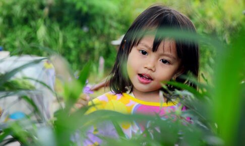 草原の中でこっちを見て笑う少女