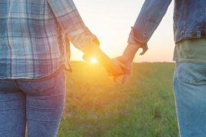 両手をつないで太陽を見つめる希望あふれる二人