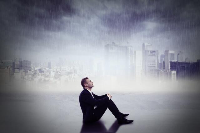 悲しいがために雨の中でも座り込んでいる孤独な男性